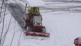 Vista aérea del tractor compacto con la nieve que ara la acera de la ciudad de la limpieza del equipo almacen de video