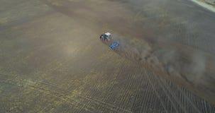Vista aérea del tractor que mueve el campo encendido cosechado 4k almacen de metraje de vídeo