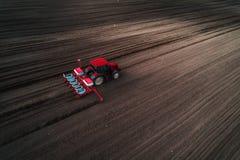 Vista aérea del tractor rojo que prepara el campo con cultivaror del seedbad Granjero que siembra la tierra Imágenes de archivo libres de regalías