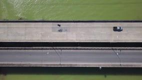 Vista aérea del transporte que se mueve a lo largo del puente sobre el río coloreado verde tropical en Tailandia Infraestructura  metrajes
