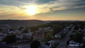 Vista aérea delantera lenta de la pequeña ciudad en la puesta del sol almacen de metraje de vídeo