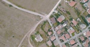 Vista aérea aérea disparada acima das casas de cidade pequena ao lado da floresta dos pinheiros vídeos de arquivo