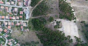 Vista aérea aérea disparada acima das casas de cidade pequena ao lado da floresta dos pinheiros video estoque