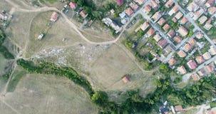 Vista aérea aérea disparada acima das casas de cidade pequena ao lado da floresta dos pinheiros filme