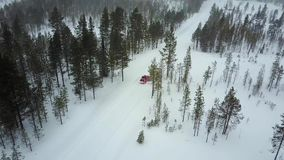 Vista aérea do único carro vermelho na estrada na paisagem bonita do inverno de Lapland durante uma queda de neve vídeos de arquivo