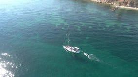 Vista aérea do barco de navigação no mar impressionante de turquesa em Halkidiki Grécia, movimento invertido pelo zangão filme