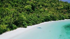 Vista aérea do barco só do banca na praia arenosa tropical da selva com água azul rasa de turquesa na lagoa de Cadlao EL video estoque