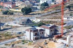 Vista aérea do canteiro, das casas de campo e dos guindastes de obras Fotos de Stock
