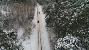 Vista aérea do carro que move-se na floresta do inverno filme