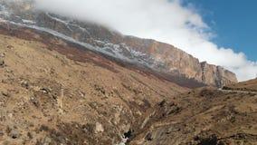 Vista aérea do desfiladeiro com uma estrada de terra e um rio da montanha nas montanhas do Cáucaso Dia ensolarado vídeos de arquivo