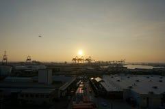 Vista aérea do por do sol, de guindastes de envio, de barco do transporte de Matson, e de avião que voa no ar fotografia de stock royalty free