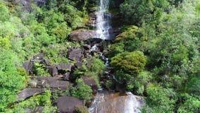 A vista aérea do rio flui abaixo da inclinação rochoso no pico do ` s de Adam em Sri Lanka filme