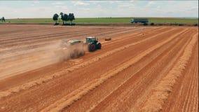 Vista aérea do trator com ceifeira de liga que faz estacas do feno Colheita da agricultura do campo de trigo e filme