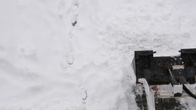 Vista aérea do trator compacto com a neve que ara o parque de estacionamento de limpeza do equipamento filme