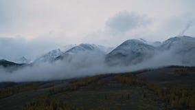 Vista aérea do vale da floresta do outono de Altay e de montanhas nevados através das nuvens filme