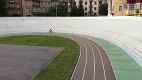 Vista aérea do velodrome Menina desportivo no velodrome Bicicleta fêmea da estrada da equitação do ciclista na trilha de ciclismo vídeos de arquivo