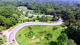 A vista aérea do zangão dos carros está atravessando uma estrada da curva na montanha com floresta verde filme