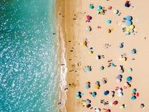 Vista aérea do zangão do voo da multidão dos povos que relaxa na praia fotografia de stock royalty free