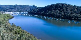 A vista aérea dos barcos amarrou no rio de Hawkesbury, Brooklyn, Austrália com água azul cercada por árvores de goma do eucalipto Fotografia de Stock