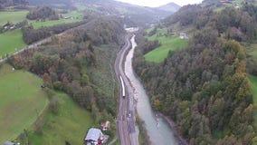 Vista aérea dos cumes em Áustria, em montanhas, em rio e em estrada de ferro vídeos de arquivo