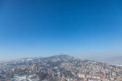 Vista aérea dos montes dos subúrbios de Sarajevo, de Bósnia e de Herzegovina durante casas de uma coberta da neve da tarde do inv imagens de stock