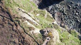 Vista aérea dos penhascos bonitos perto do farol sul histórico da pilha em Anglesey - Gales filme