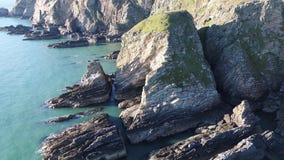 Vista aérea dos penhascos bonitos perto do farol sul histórico da pilha em Anglesey - Gales video estoque