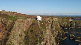 Vista aérea dos penhascos bonitos perto do farol sul histórico da pilha em Anglesey - Gales vídeos de arquivo