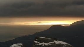 Vista aérea em silhuetas da montanha perto do mar na névoa contra as nuvens cinzentas escuras no por do sol tiro fascinar video estoque
