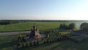 Vista aérea em torno da igreja contra o contexto de um campo e de uma floresta vídeos de arquivo