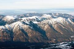 Vista aérea em um grupo da montanha com partes superiores cobertos de neve Imagens de Stock Royalty Free