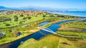 Vista aérea em uma ponte bonita através de um rio pequeno com subúrbio residencial e mar de Tasman no fundo Em algum lugar em Nov imagens de stock