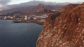 Vista aérea hermosa de la costa sur de Tenerife y de la ciudad de Los Cristianos en la puesta del sol almacen de video