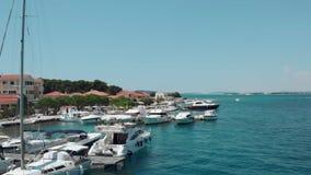 Vista aérea hermosa de un pequeño puerto deportivo con los barcos y la gente que nadan en la playa metrajes