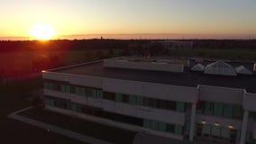 Vista aérea hermosa del edificio de oficinas corporativo en el tiempo de la puesta del sol de la oscuridad almacen de metraje de vídeo