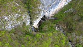 Vista aérea 4k de una cascada y de una entrada grande de la cueva por el abejón almacen de video