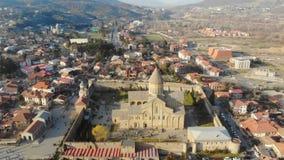 vista aérea 4k del cierre ortodoxo famoso de la catedral de Svetitskhoveli para arriba y detrás panorama de la ciudad de Mtskheta almacen de metraje de vídeo