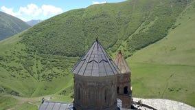 Vista aérea a la iglesia de la trinidad de Gergeti cerca del pueblo Gergeti en Georgia, debajo del soporte Kazbegi almacen de metraje de vídeo