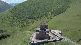 Vista aérea a la iglesia de la trinidad de Gergeti cerca del pueblo Gergeti en Georgia, debajo del soporte Kazbegi almacen de video