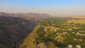 Vista aérea maravillosa del valle de la montaña y del pueblo armenio viejo el día soleado almacen de video