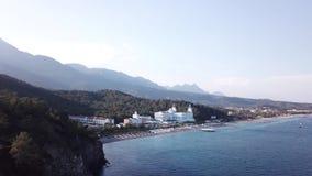 Vista aérea no litoral com o hotel de luxo com fundo da floresta e das montanhas e o céu azul vídeo Parte superior bonita do verã video estoque