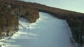 Vista aérea: Os esquiadores vão abaixo da inclinação vídeos de arquivo