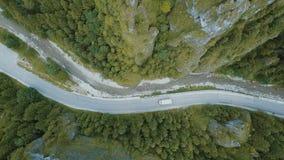 Vista aérea panorámica superior de un camión que mueve encendido un camino de la montaña en una garganta profunda hermosa almacen de video