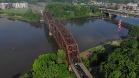 Vista aérea reversa lenta de la pequeña ciudad los E.E.U.U. y del puente del ferrocarril almacen de metraje de vídeo