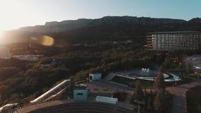 Vista aérea sobre o hotel caro na costa de mar na frente das montanhas no por do sol vídeos de arquivo