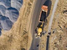 A vista aérea superior da máquina escavadora industrial pôs o asfalto na trilha do descarregador para reparar a estrada f fotografia de stock royalty free