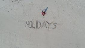 Vista aérea superior del ` de los días de fiesta del ` escrito en la arena en la playa y la mujer que se sientan en la toalla Imágenes de archivo libres de regalías