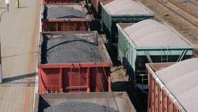 A vista aérea UHD do trem de mercadorias com vagões e a posição treinam com carvão video estoque