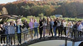 Vista aérea um o grande grupo de adolescentes nos suportes do parque na ponte, e danças e poses na câmera Novo maravilhoso vídeos de arquivo