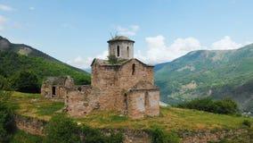 Vista aérea uma igreja cristã parcialmente destruída antiga do ANÚNCIO do século X nas montanhas caucasianos do filme
